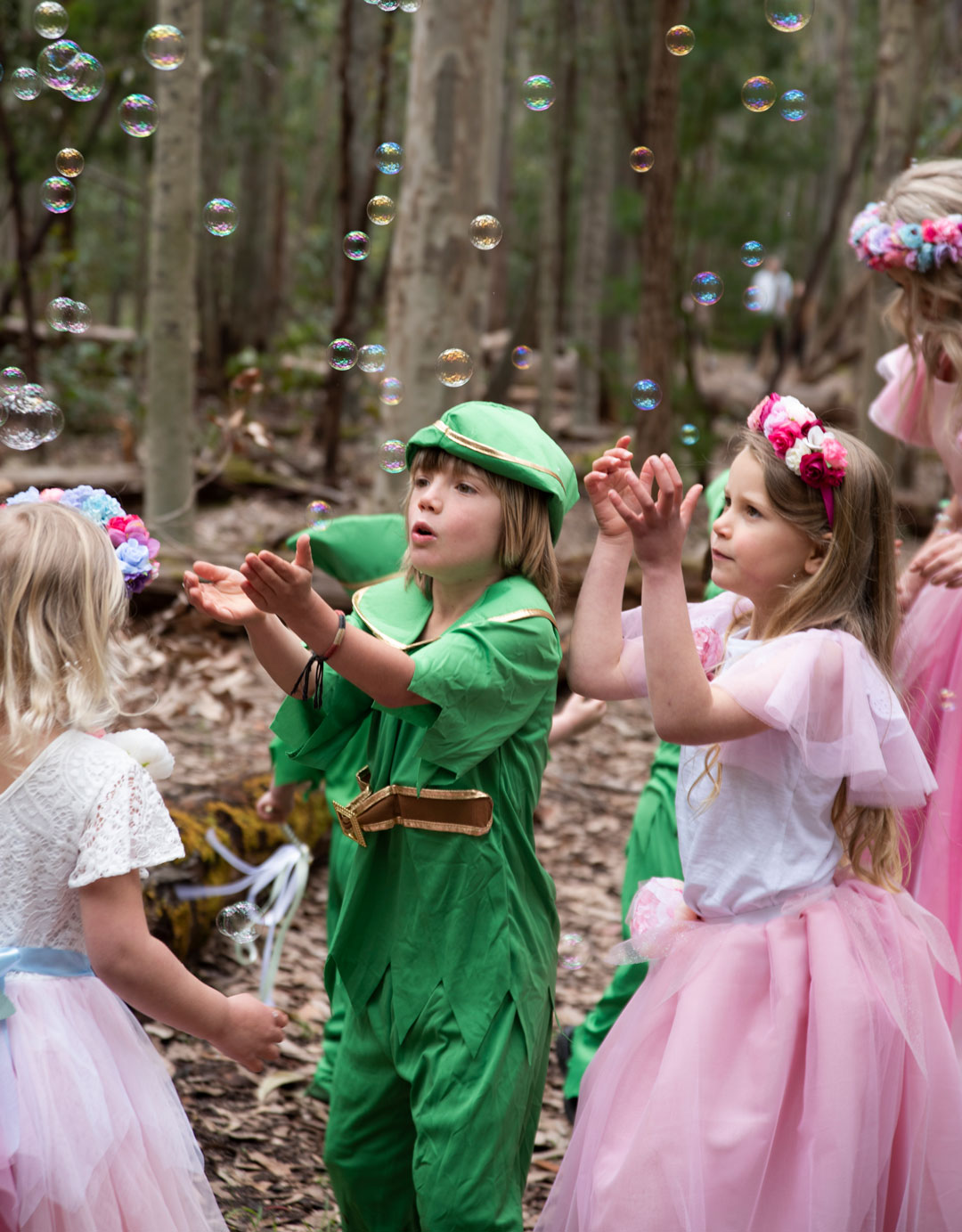 Pixies and fairy children playing with bubbles at party