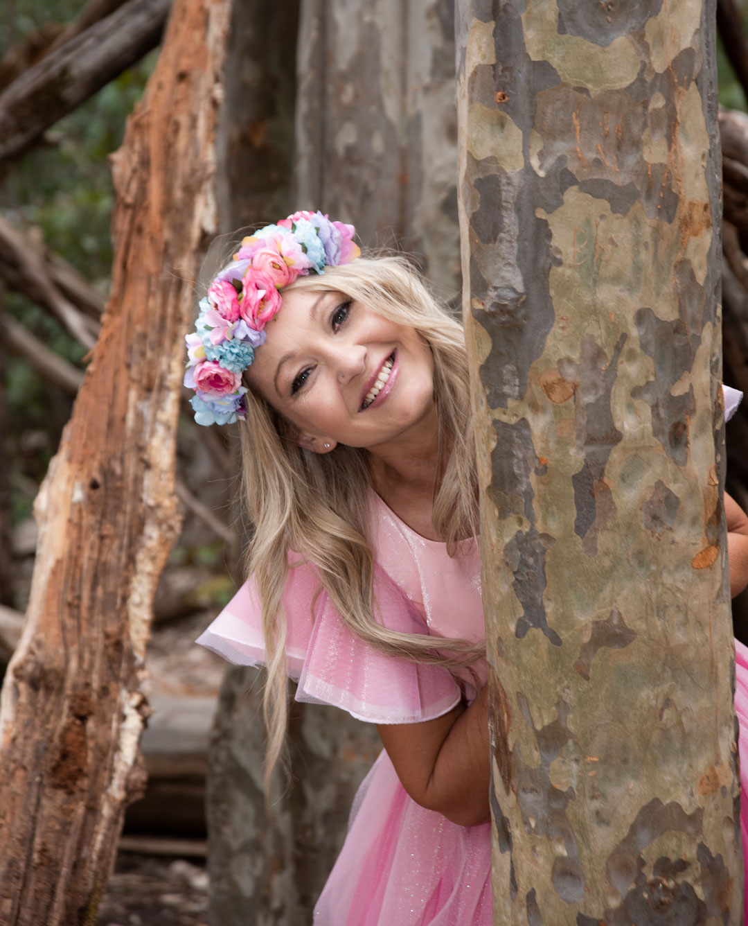Fairybelle peeking out from behind a tree